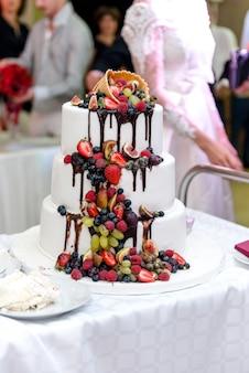 結婚式のテーブルの上のスタンドにフルーツと白い結婚式の大きなケーキ。