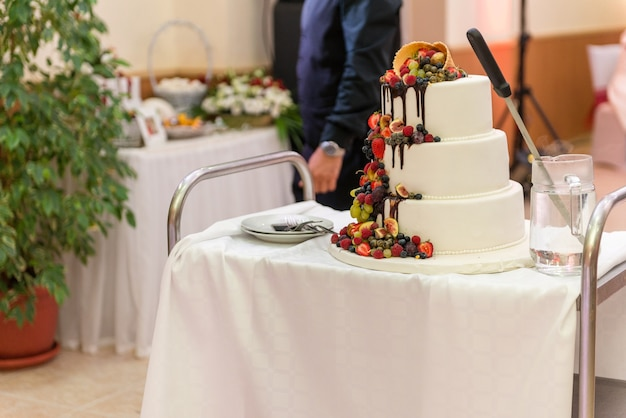 White wedding big cake with fruit on stands on the wedding table.
