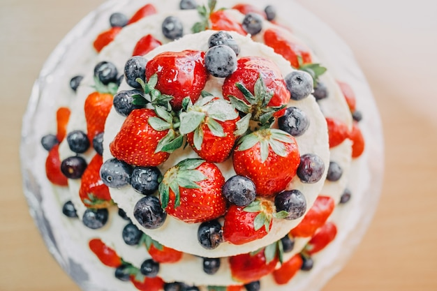 White wedding cake decorated with cherries, strawberries and blueberries