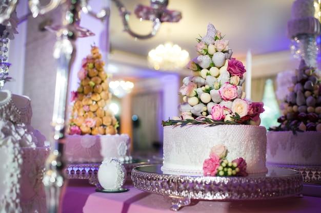スタンドにクリーム色の花で飾られた白いウエディングケーキ。