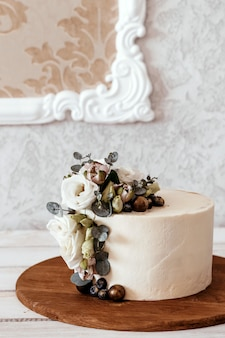 White wedding cake decorated with eustoma and eucalyptus flowers. place for text.