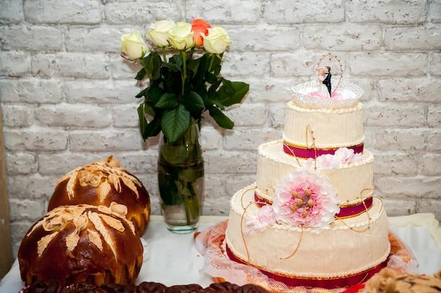 花と特別な式典のパンまたはパンと白いウエディングケーキ。結婚式のコンセプト。閉じる。
