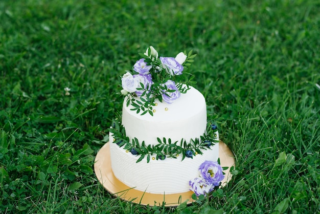 White wedding cake with lilac flowers and sprigs of greenery with flowers