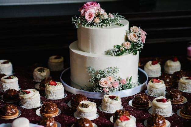 Белый свадебный торт с розовыми цветами и зеленью на праздничном столе с французской выпечкой