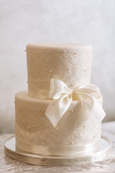 White wedding cake with ribbon and pearls
