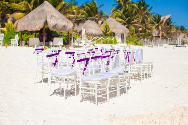 White wedding chairs decorated with purple bows on sandy beach