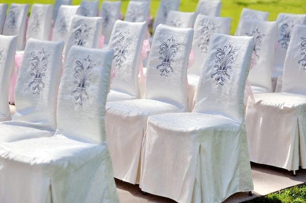 White wedding chairs in summer park on ceremony bride and groom