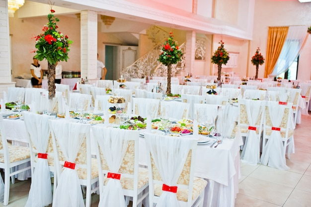 White wedding decor on chair in restaurant with red ribbons