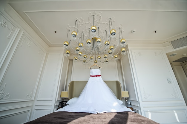 White wedding dress of the bride hanging on the chandelier in the hotel room