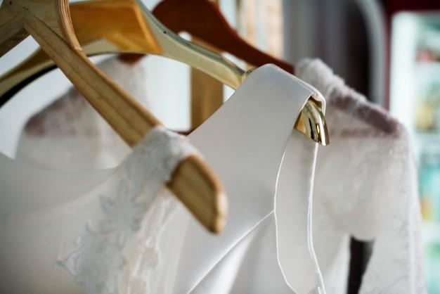 Белое свадебное платье висит у окна