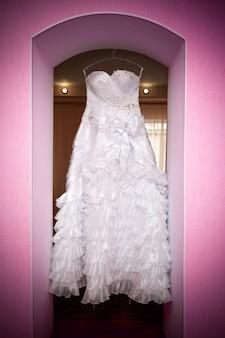 Белое свадебное платье висит на плечах. мягкий свет и цвета