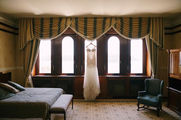 白いウェディングドレスがホテルの部屋の窓にぶら下がっています