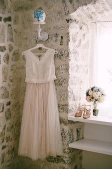 白いウェディングドレスは、サンダルとブライダルブーケの横にある窓にぶら下がっています