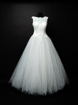 Белое свадебное платье на черном фоне в студии