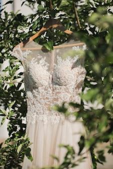 森の木からぶら下がっているハンガーの白いウェディングドレス