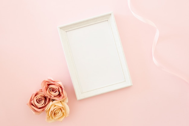 White wedding frame with roses on a pink background