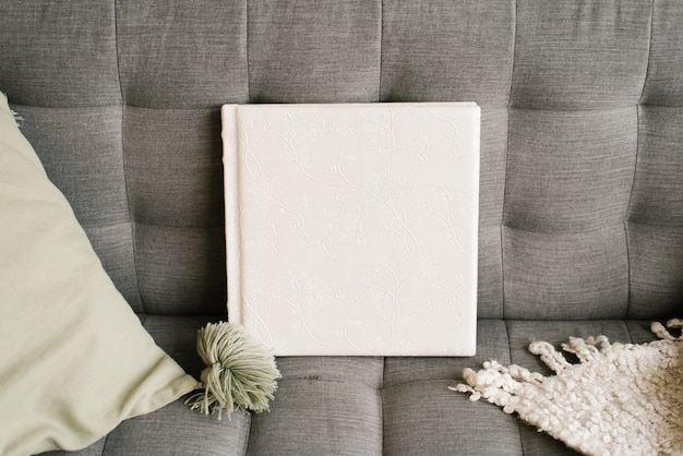 White wedding photo book in a leather cover in sofa