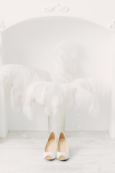 White wedding shoes over the fireplace and ostrich feathers in white interior