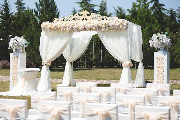 야외 행사에 하얀 웨딩 텐트. 아치. 의자.