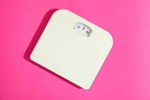 ピンクの背景、テキスト用のスペースに白の体重計