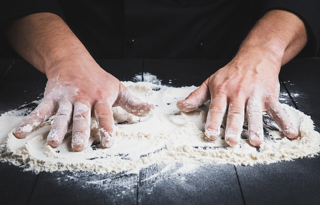 White wheat flour on a black wooden table and two male hands