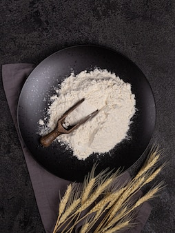 黒い石で作られたプレート上の暗い構造の背景に木のスプーンで白い小麦粉