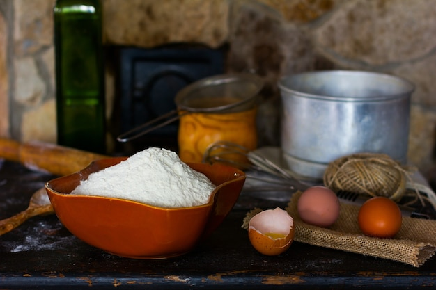 Белая пшеничная мука в керамической посуде, разбитое яйцо с желтком, целые яйца и кухонная утварь