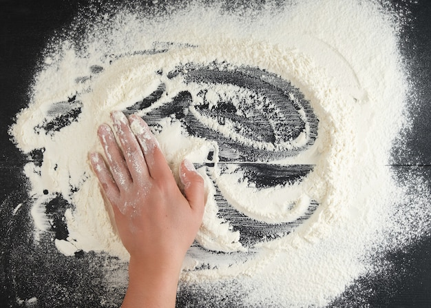 White wheat flour scattered on a black surface