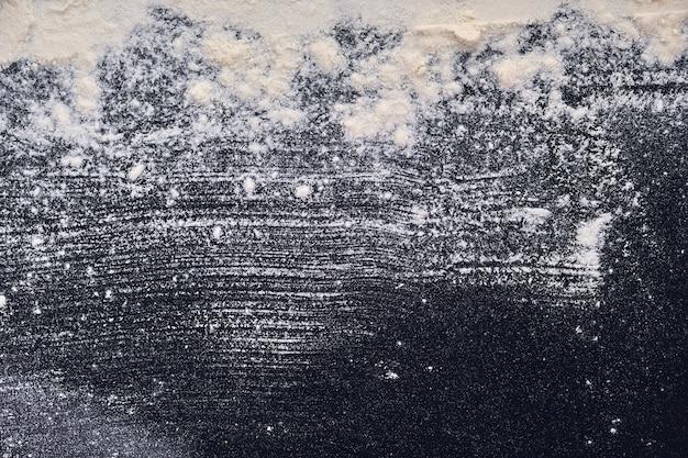 블랙 테이블에 흩어져있는 흰 밀가루