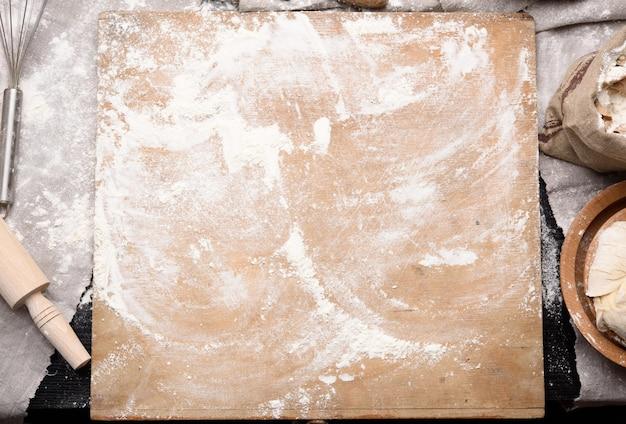 Белая пшеничная мука, деревянная скалка и старая разделочная доска на столе, вид сверху