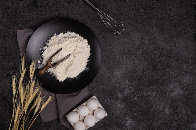 White wheat flour in a wooden spoon on a dark structural background on a plate made of black stone