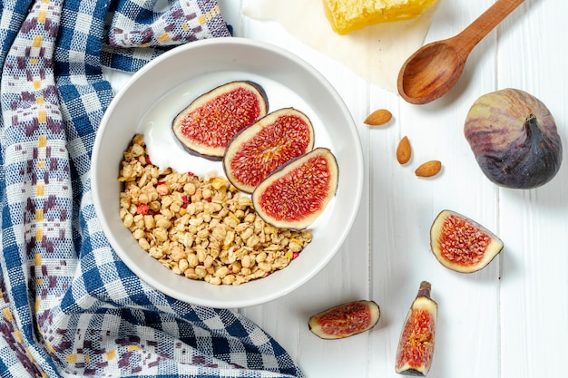 White wheat granola with low-fat yogurt in a white bowl in a composition with a spoon, honeycombs and fig on white wooden background.