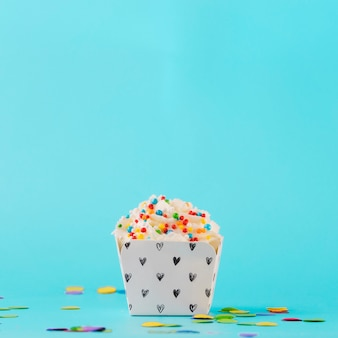 White whipped cream with colorful sprinkles and confetti against blue background