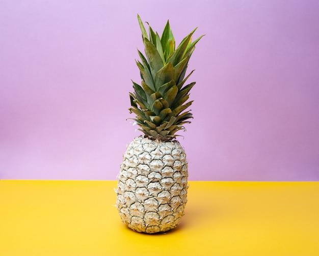 Белый цельный свежий ананас на столе в современной студии на фиолетово-желтом фоне
