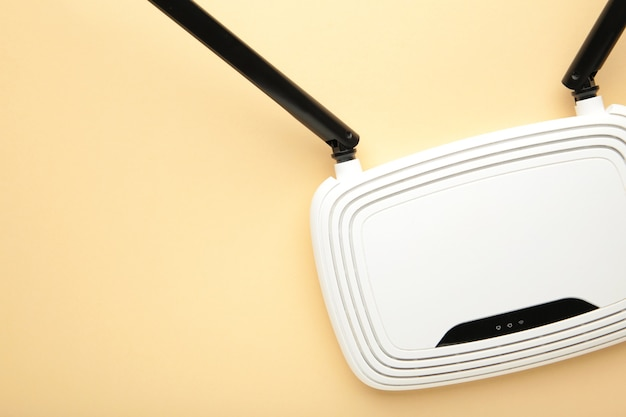 White wi-fi router with black antennas on beige surface with copy space