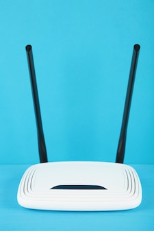 White wi-fi router with black antennas on blue background with copy space. minimalism. vertical photo