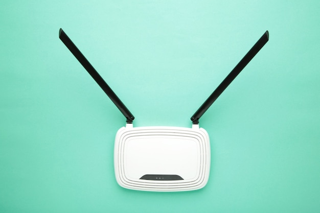 White wi-fi router with black antennas on mint surface with copy space