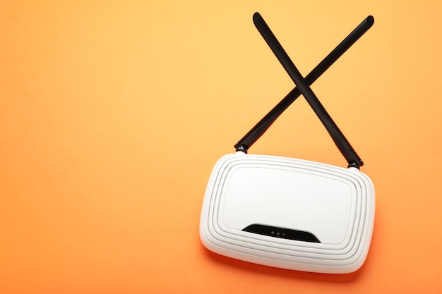 White wi-fi router with black antennas on orange surface with copy space