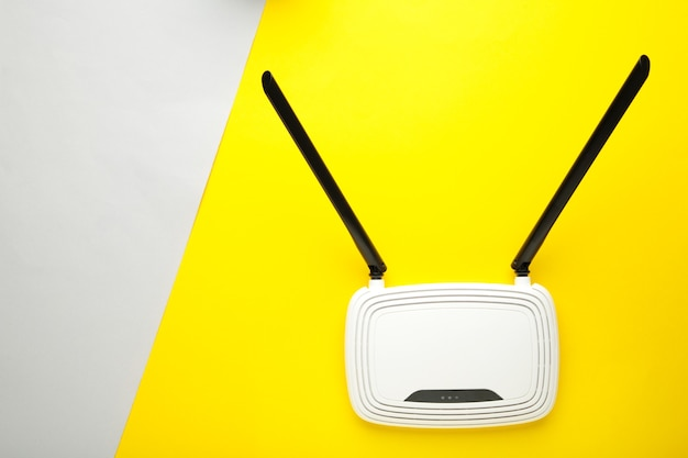 White wi-fi router with black antennas on yellow grey surface with copy space