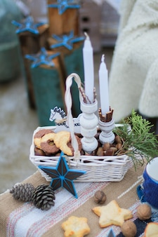 White wicker basket, with cookies and nuts and a sprig of spruce