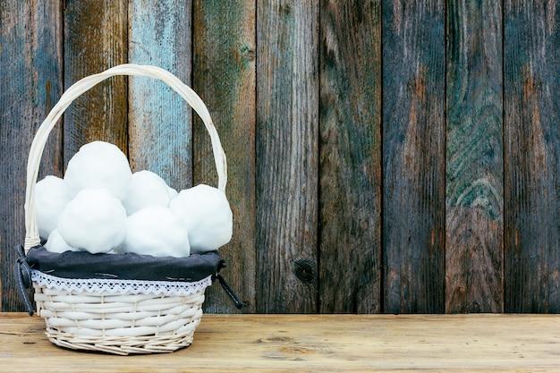Белая плетеная корзина со снежками на деревянном ретро гранж-фоне из сарая