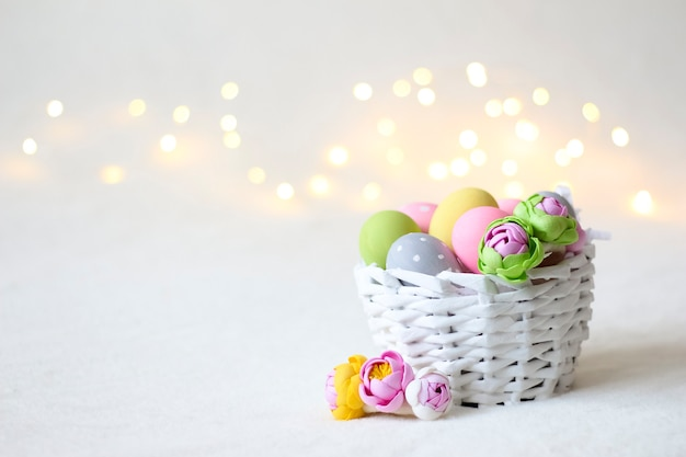 A white wicker easter basket with colorful eggs and bokeh lights in the background.