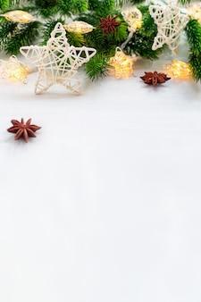 白い籐の星、クリスマスツリーの枝と花輪のライトが木製の垂直の背景にテキスト用のコピースペース、クローズアップでお祝いの装飾。