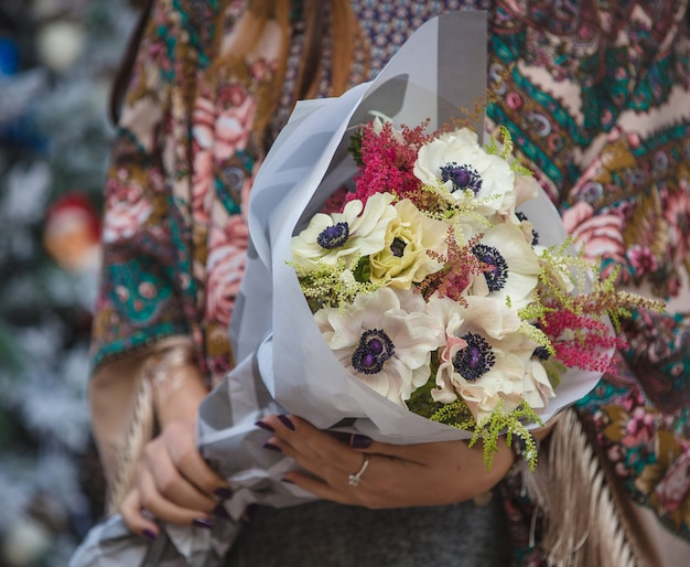 White windflowers bouquet in the hands of a woman in soho shawl