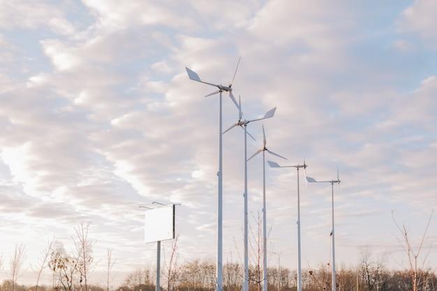 Белые ветряные мельницы и голубое небо с облаками.