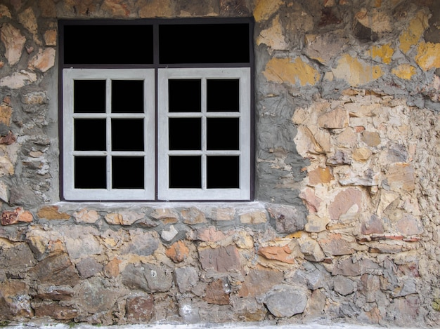 White window frame on the wall of a house made of stone.