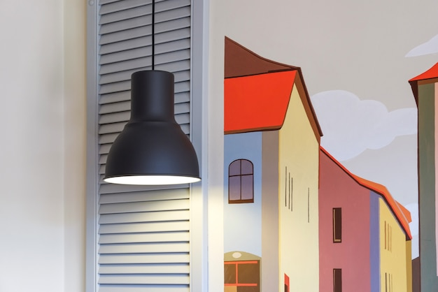 흰색 벽돌 벽 배경에 흰색 창입니다. 창 위에 램프가 빛납니다.