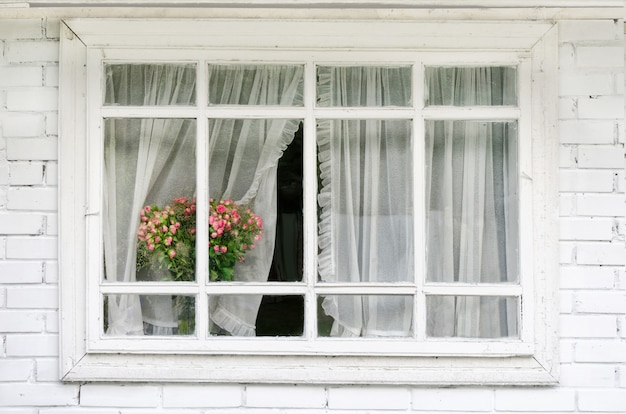 White window with curtains, a bouquet of flowers on the windowsil