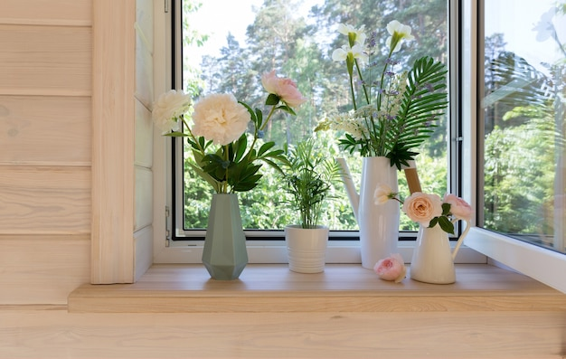 정원이 내려다보이는 소박한 목조 주택에 모기장이 있는 흰색 창문. 창턱에 있는 세련된 스칸디나비아 물뿌리개에 흰색 창포, 장미, 모란, 루핀 꽃 꽃다발