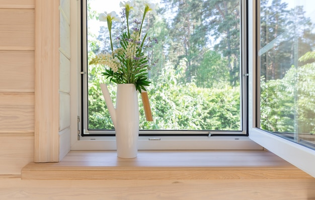 White window with mosquito net in a rustic wooden house overlooking the garden, pine forest. bouquet of white irises and lupins flowers in a stylish scandinavian watering can on the windowsill